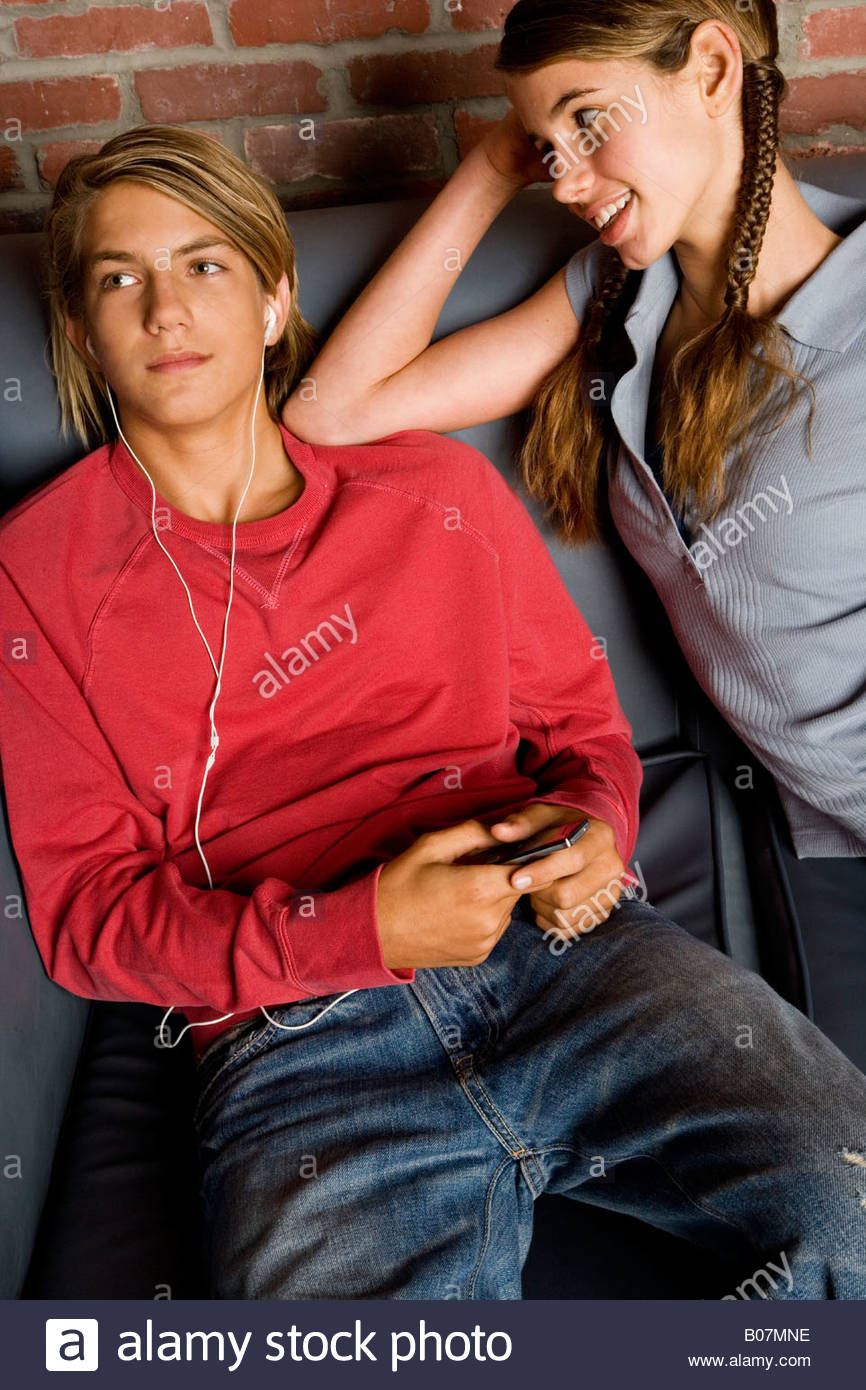 Teenage boy and girl seated, boy listening to music on mp3 - Stock Image