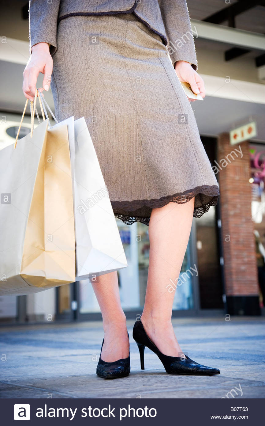 Woman in a business suit holding shopping bags in the street - Stock Image