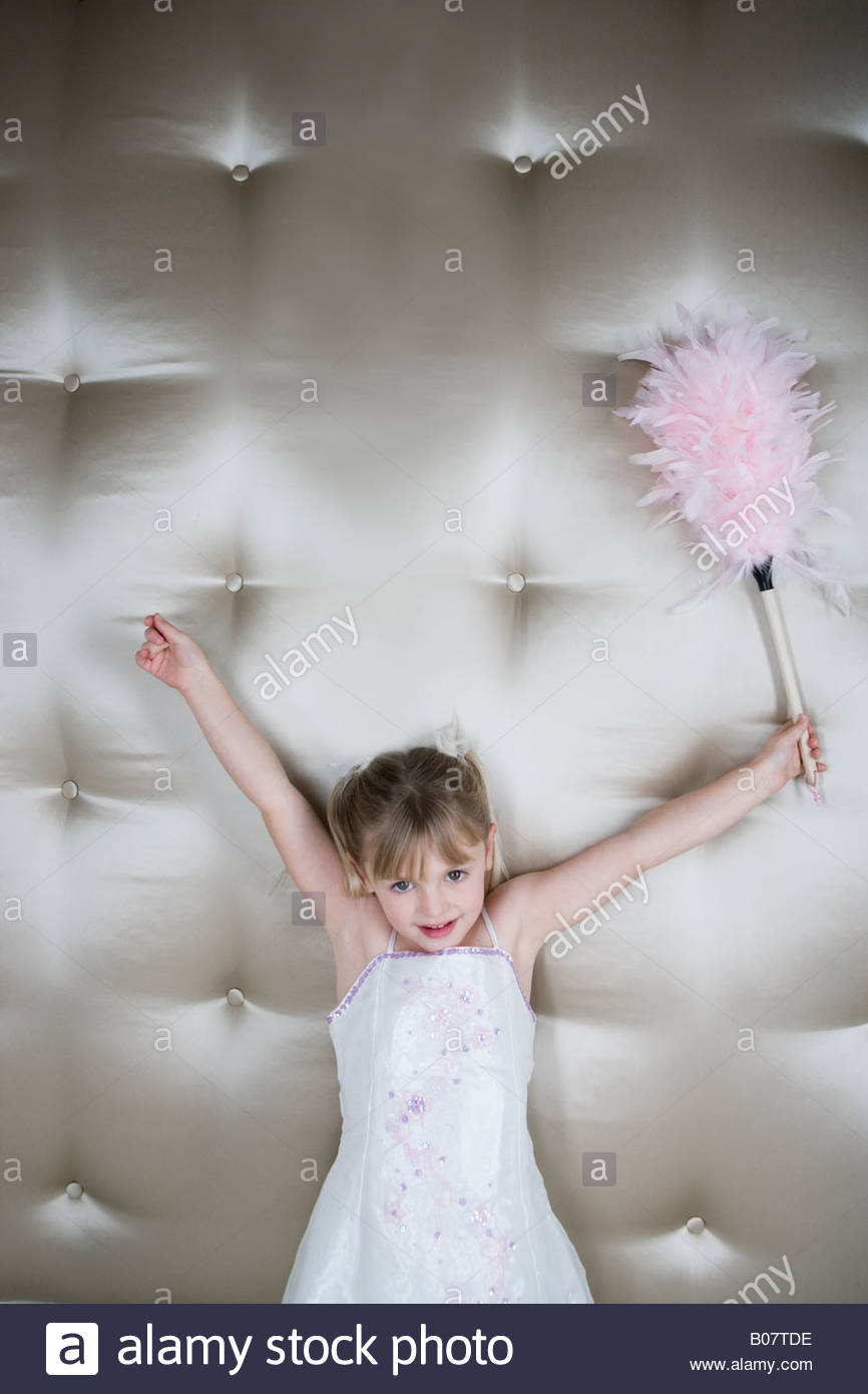 Little girl in a party dress holding a pink feather duster - Stock Image