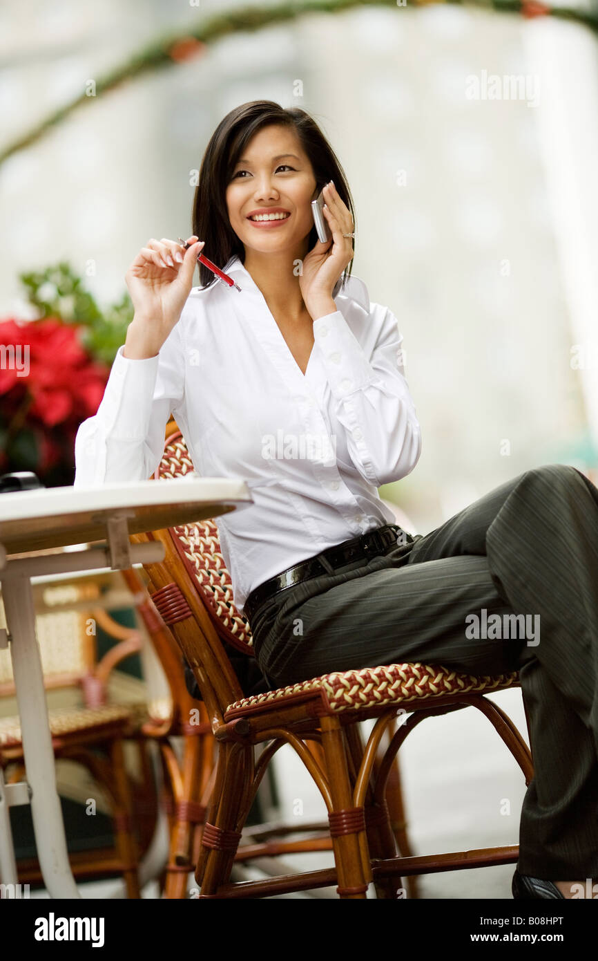 A young woman is sitting at a table seemingly chatting on the phone. Stock Photo