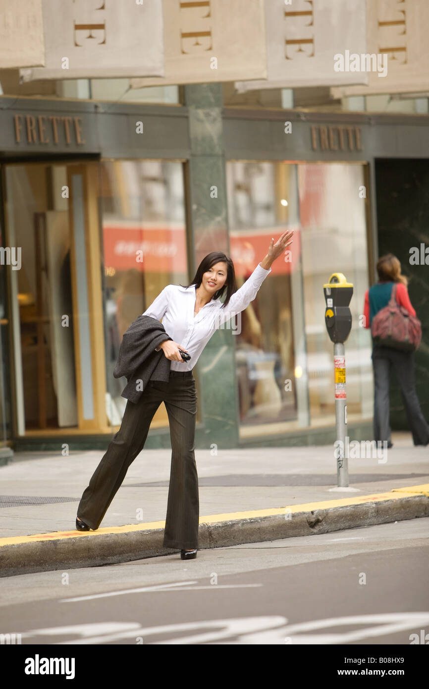 A young woman is hailing a taxi in a city street. - Stock Image