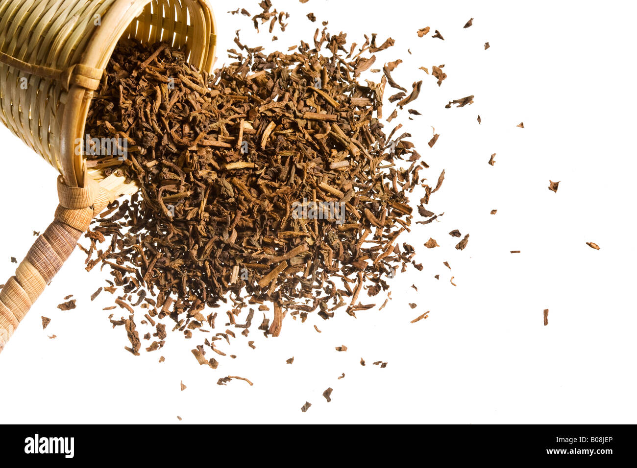 An overflowing heap of raw tea spills out of a woven scooper. - Stock Image