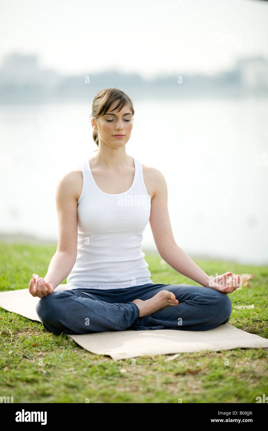 A young woman is sitting in lotus position on a yoga mat in a park. - Stock Image