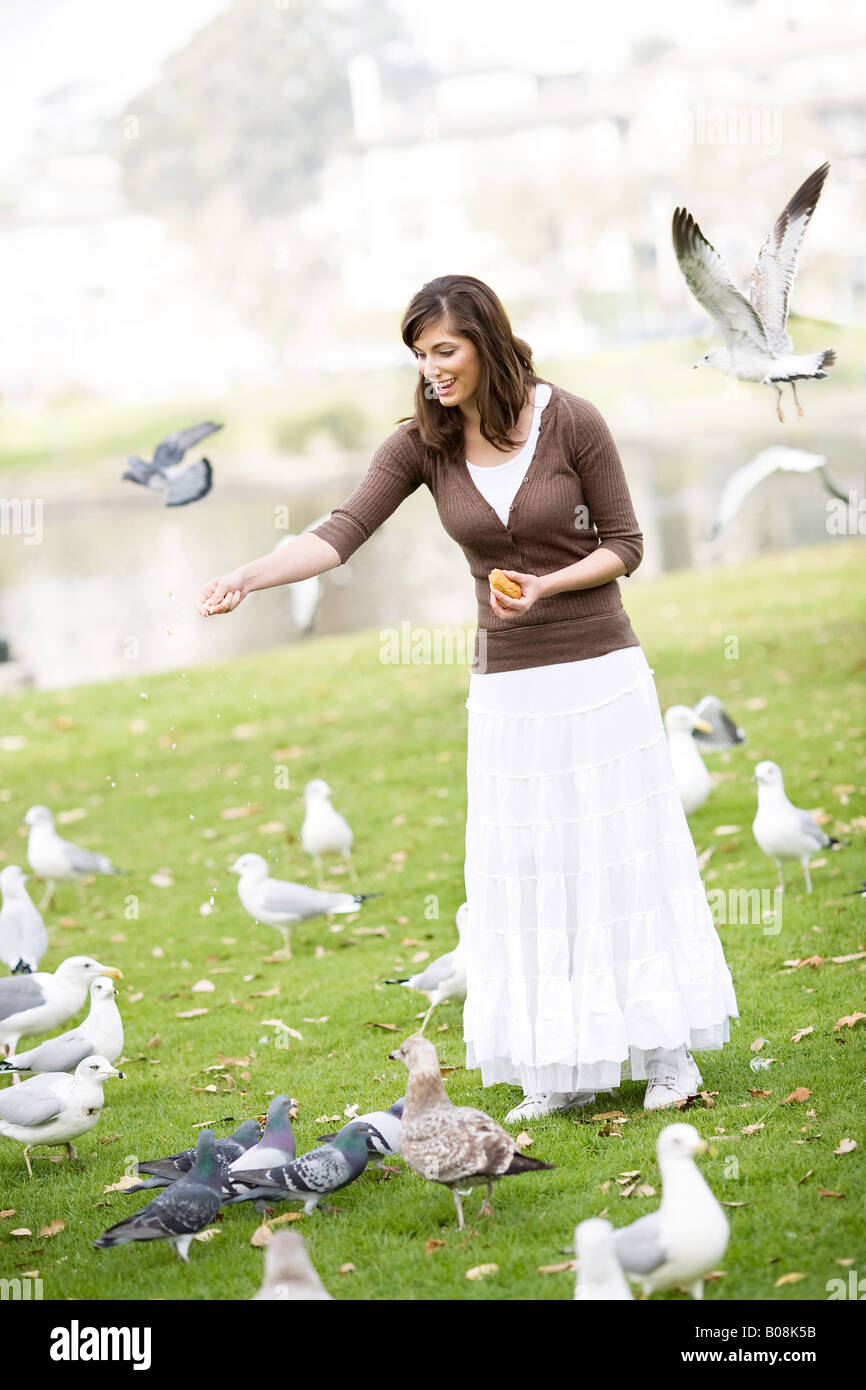 A young woman is standing in a park tossing food to the many gathering birds. - Stock Image