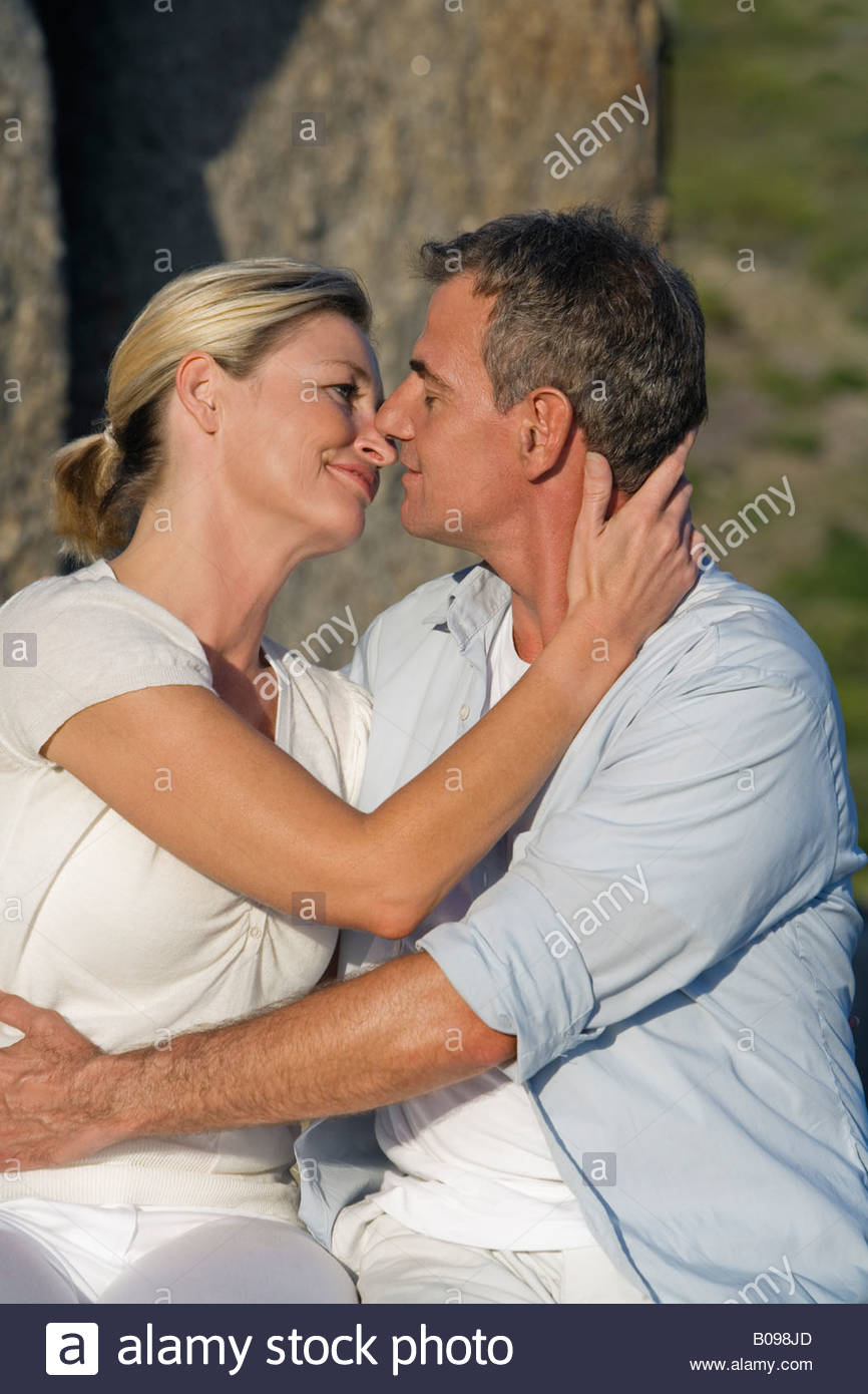 mature couple sitting on rock, embracing and kissing, portrait stock
