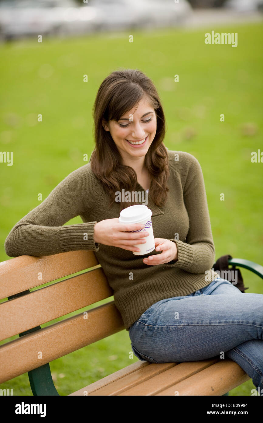 A woman is smiling while sitting on a park bench holding a drink - Stock Image