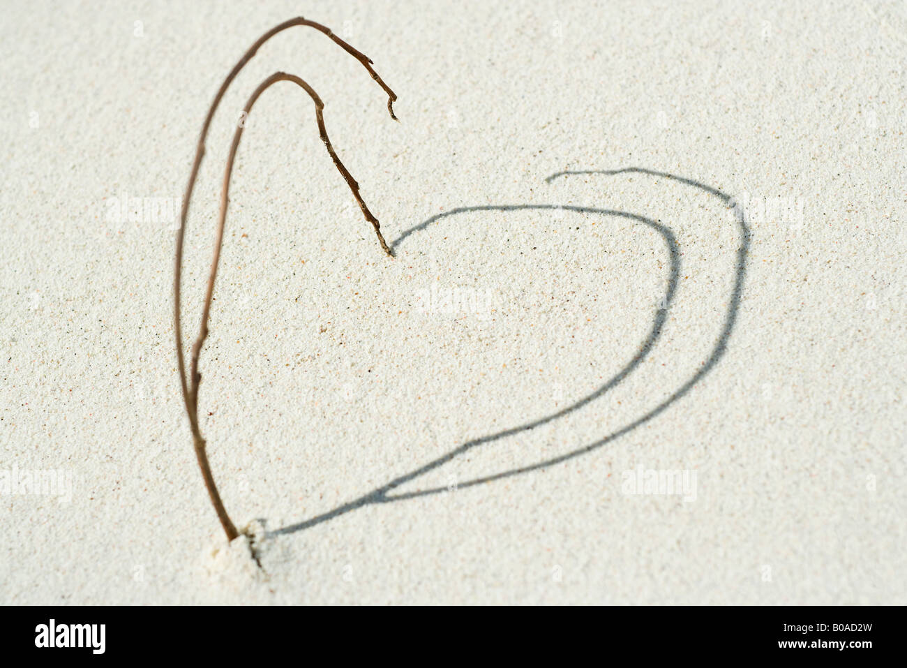 Twigs and shadows arranged in heart shape on the beach, close-up Stock Photo