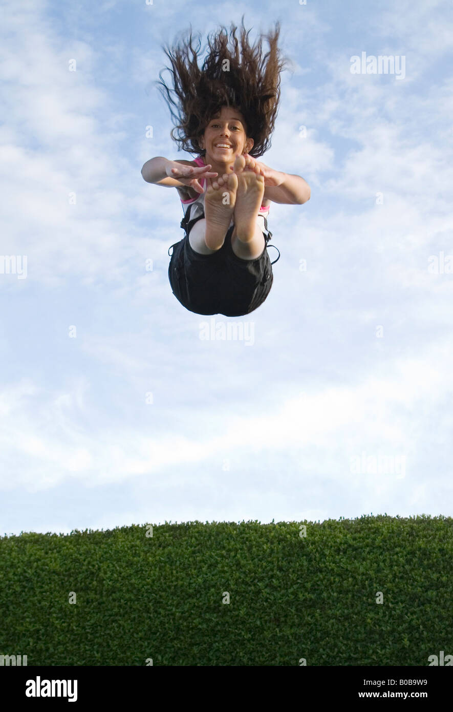 a-teenage-girl-jumping-and-descending-on-a-trampoline-uk-B0B9W9.jpg