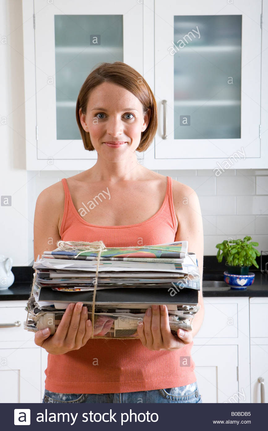 Young woman with newspaper bundle in kitchen, portrait, close-up - Stock Image