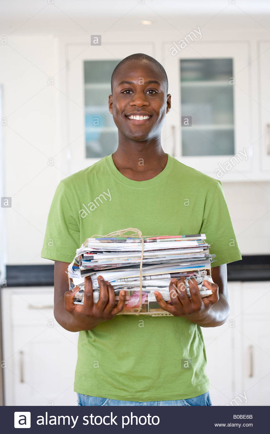 Young man with bundle of newspapers, smiling, portrait - Stock Image