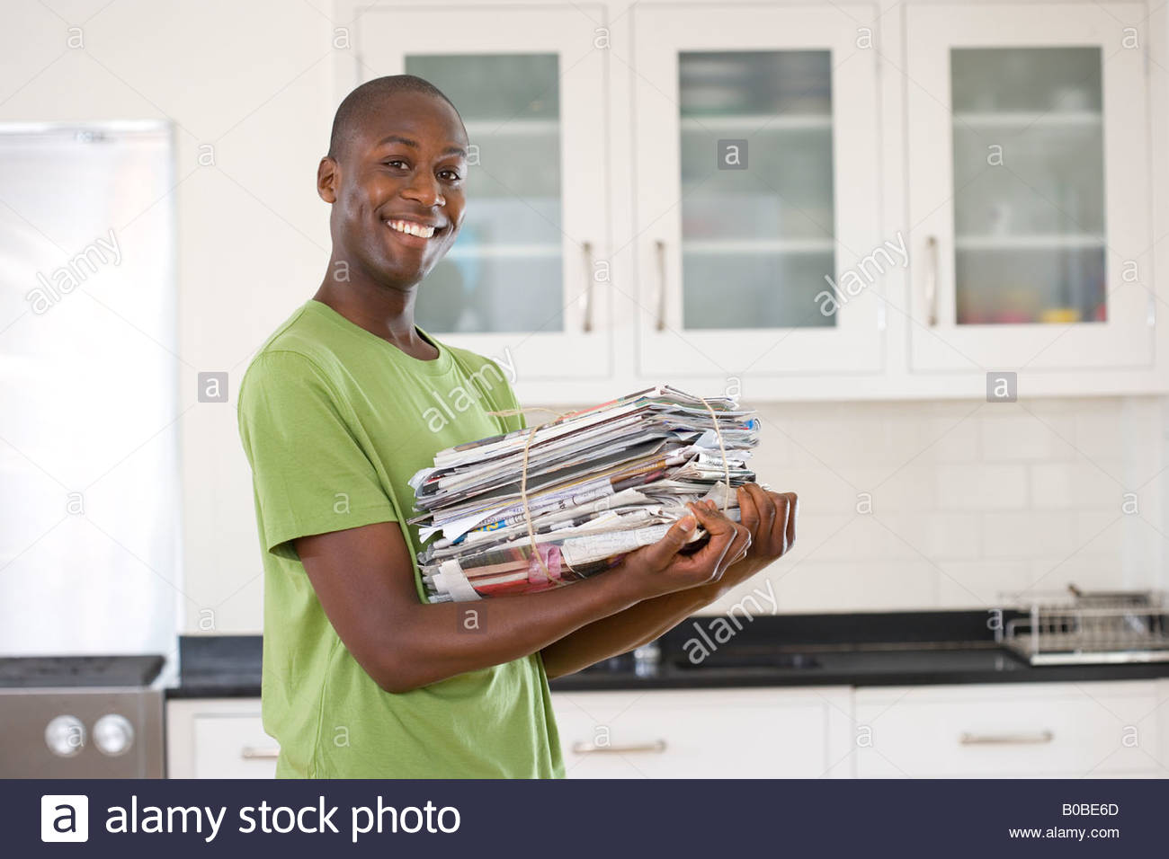Young man with bundle of newspapers in kitchen, smiling, portrait - Stock Image