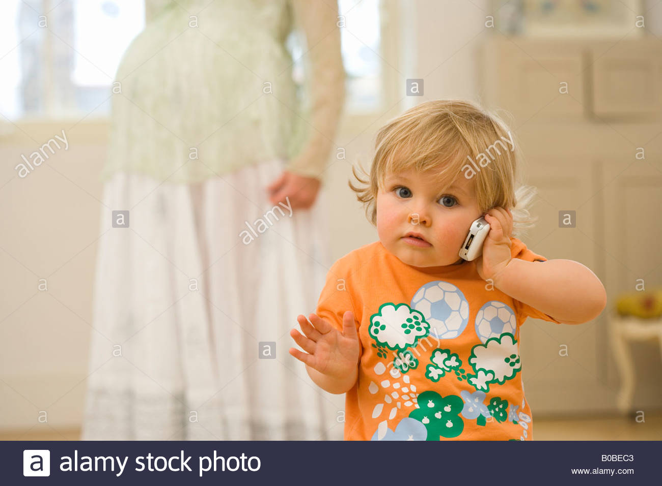 Male toddler 15-18 months using mobile phone, portrait, pregnant mother in background - Stock Image