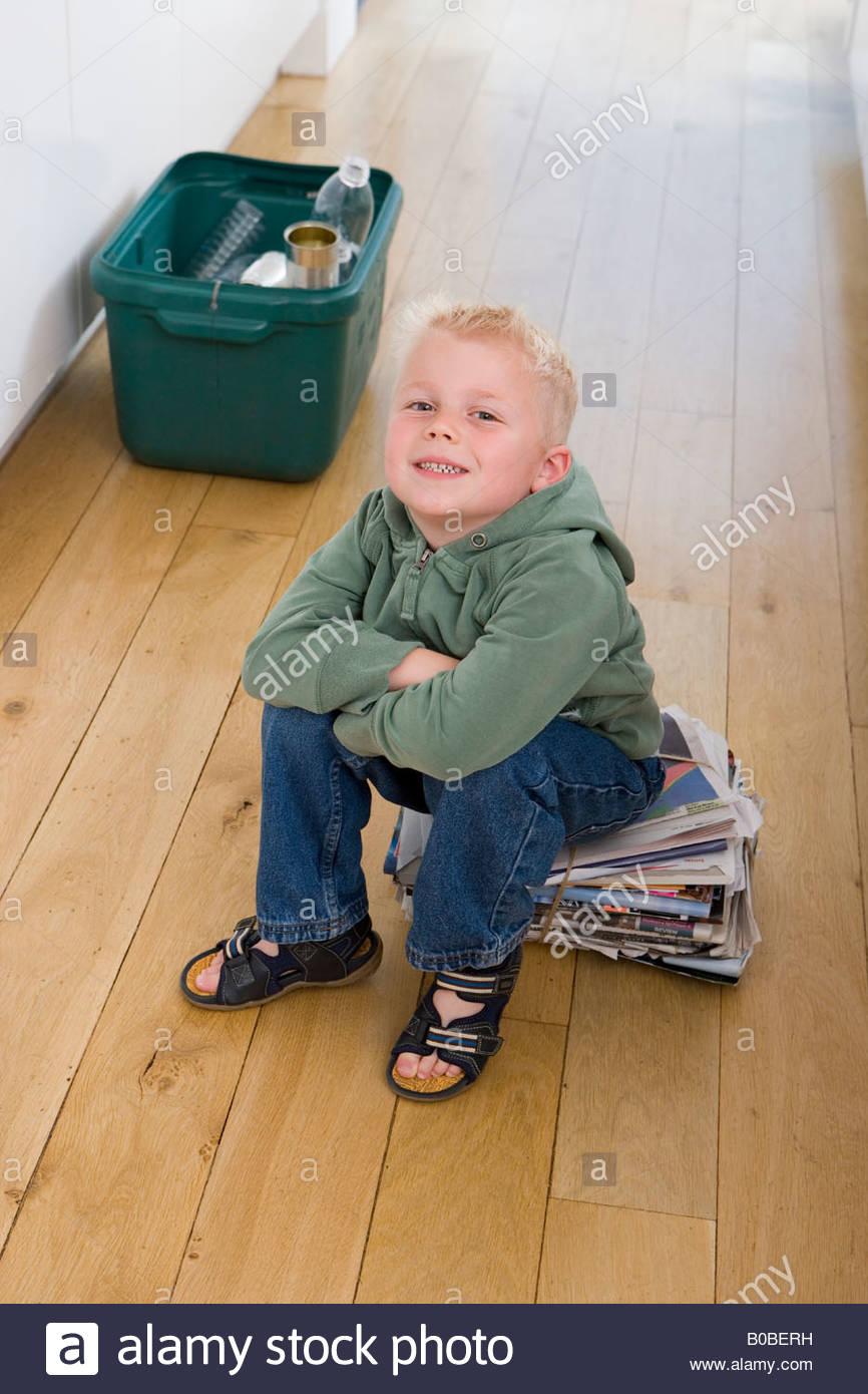 Boy 2-4 on newspaper bundle by recycling bin, smiling, portrait - Stock Image