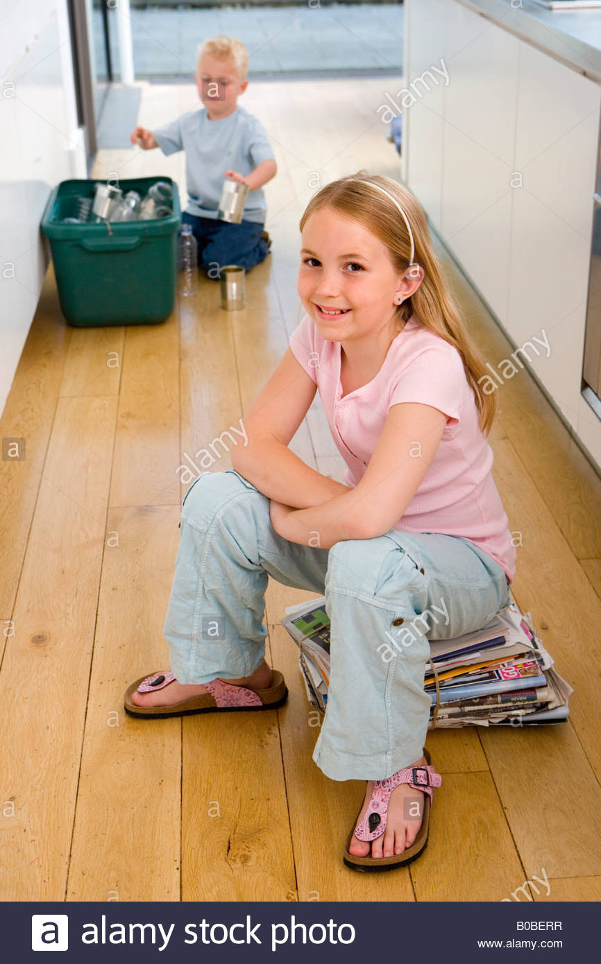 Girl  on newspaper bundle in kitchen, brother 2-4 putting recycling into bin in background - Stock Image