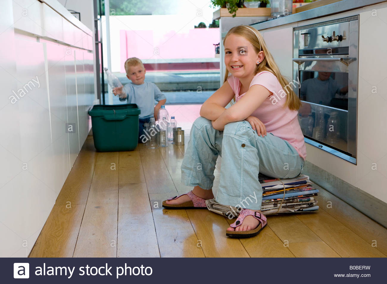Girl  on newspaper bundle in kitchen, brother 2-4 putting recycling into bin in background, smiling, portrait - Stock Image