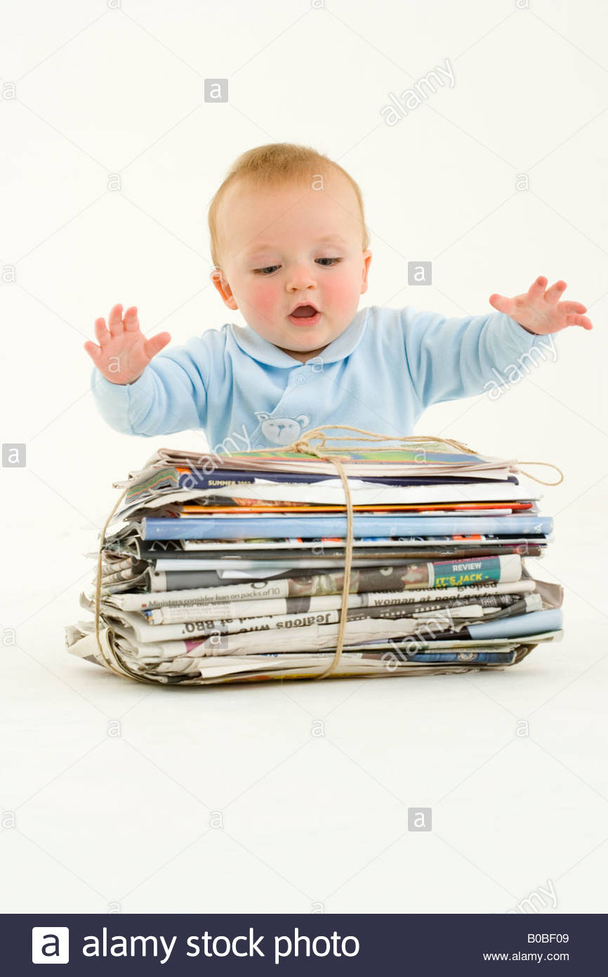 Baby boy 3-6 months with arms stretched over bundle of newspapers - Stock Image