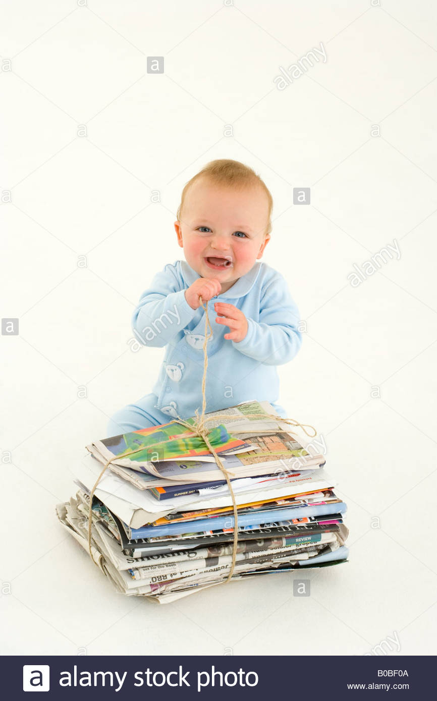 Baby boy 3-6 months by bundle of newspapers, smiling, elevated view - Stock Image