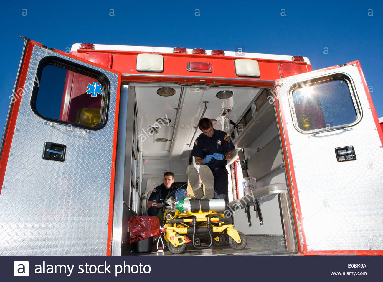 Paramedics with man on stretcher in ambulance, low angle view - Stock Image