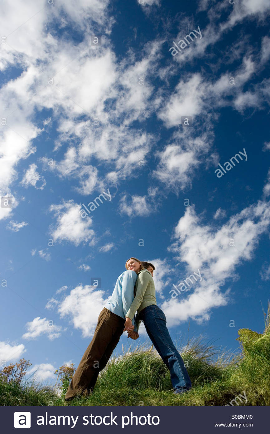 Couple leaning against each other outdoors, low angle view - Stock Image