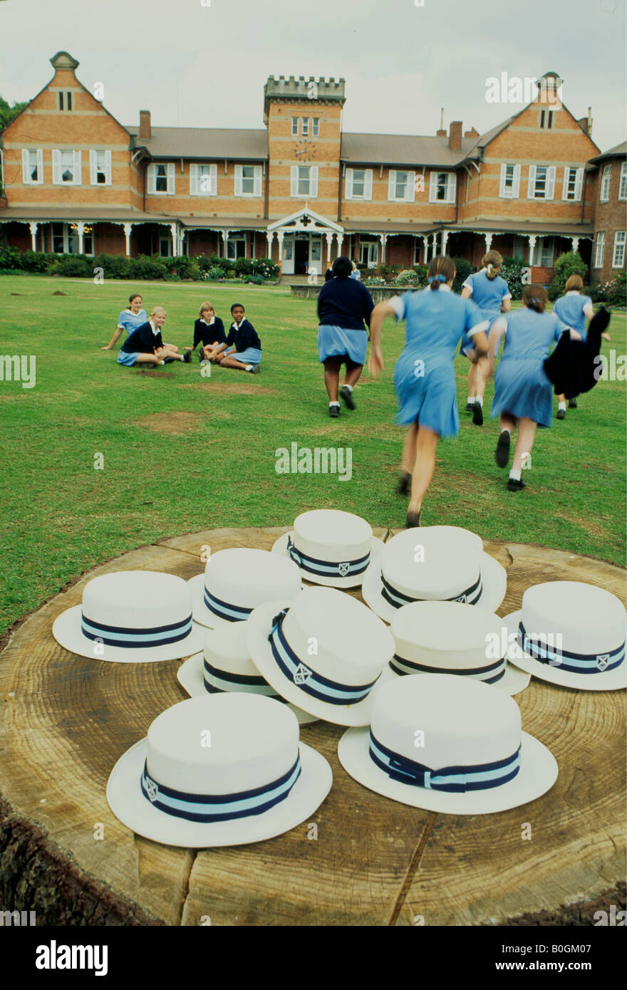 hats on a tree stump in front of girls outside a private school