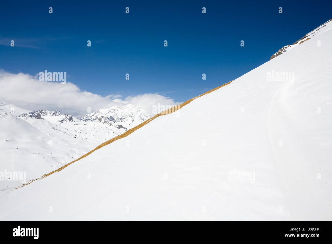 Diagonal line of orange brown rocks divides a blue-sky landscape of snow-capped Val-d'Isère mountains - Stock Image
