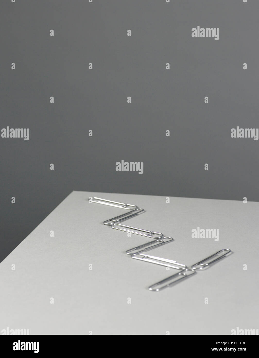 paper clips on grey background - Stock Image