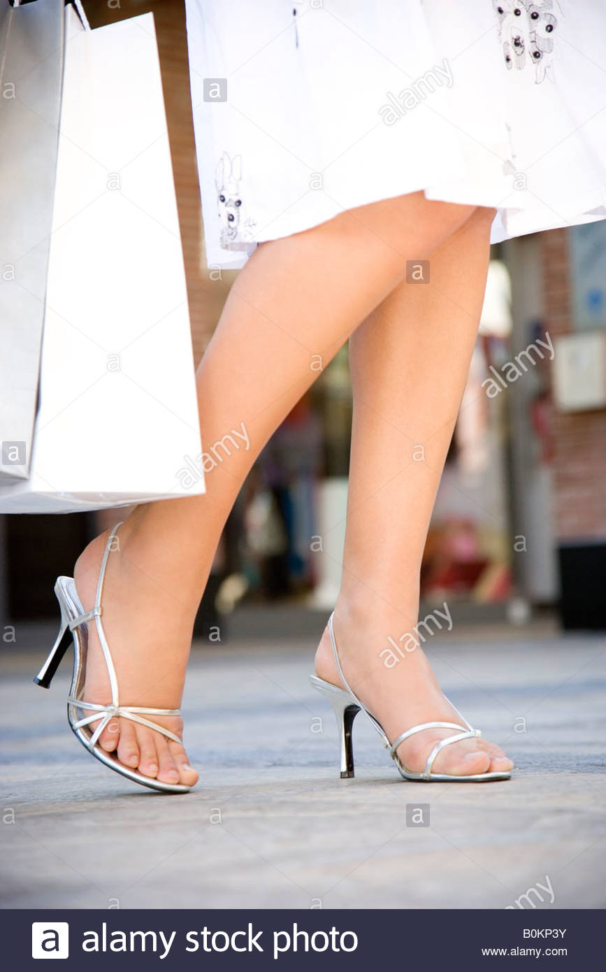 Woman holding shopping bags in the street, close-up of legs - Stock Image