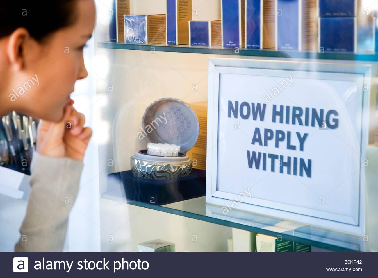 Woman looking at job advert in shop window - Stock Image