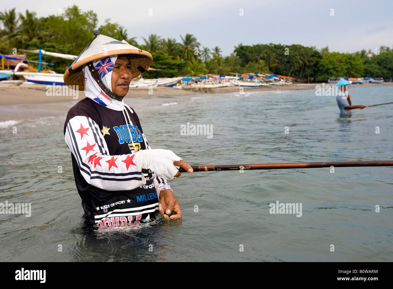 Old fisherman standing in the sea near Senggigi angling for small fish using traditional methods, Lombok Island, - Stock Image