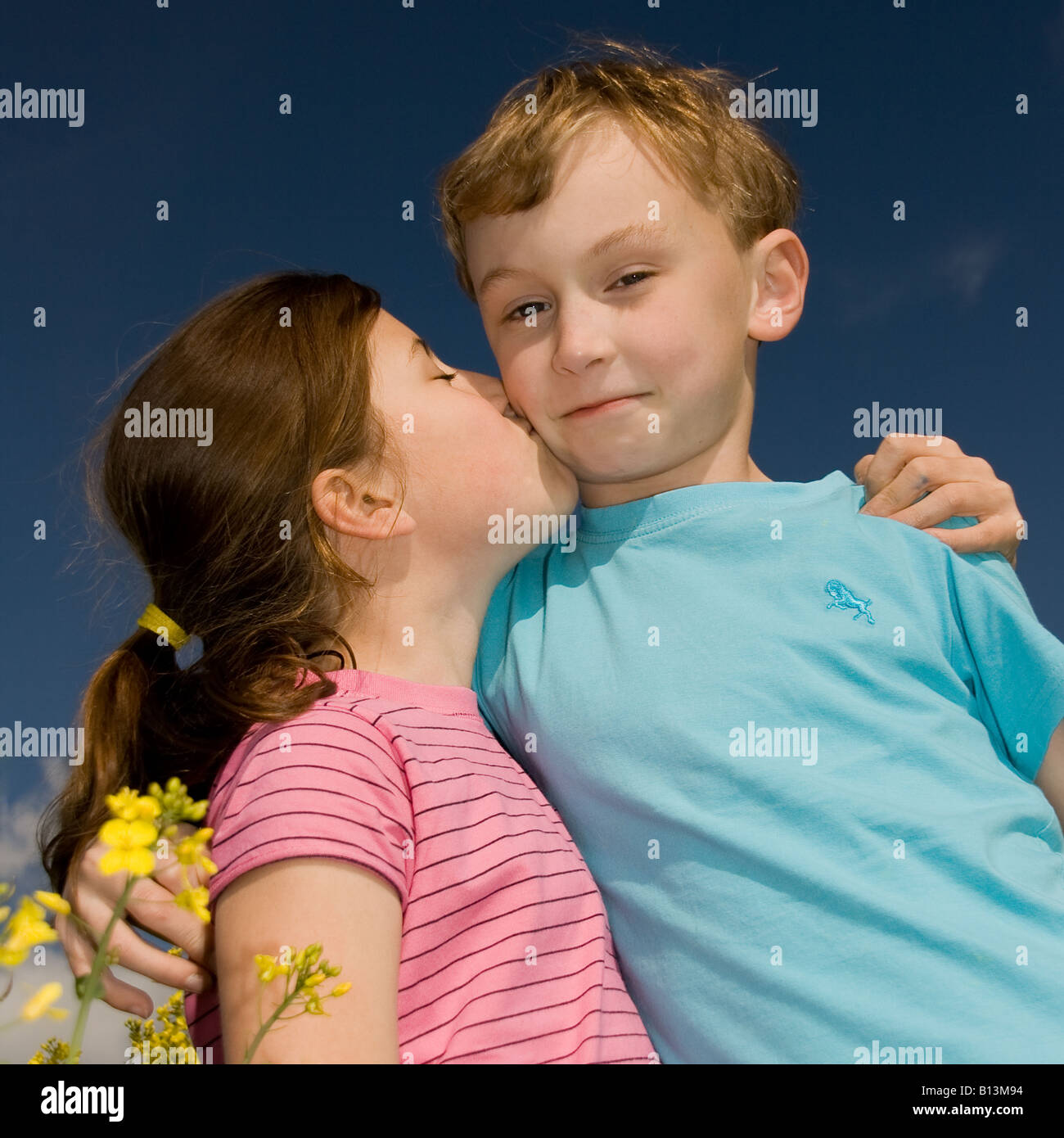 Young Boy And Girl Kissing In A Summer Field Stock Photo 17906816