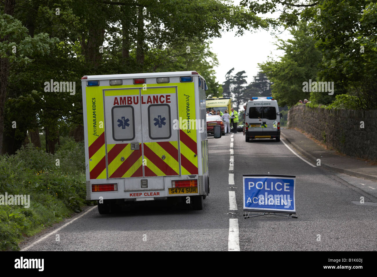 paramedic private ambulance passes police accident temporary sign in the middle of the road at the scene of a road - Stock Image