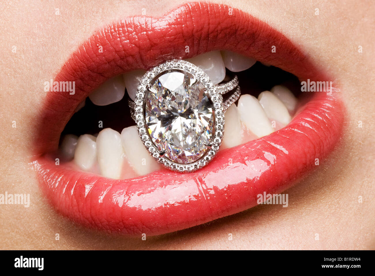 A womans mouth holding a giant diamond ring with her teeth. - Stock Image
