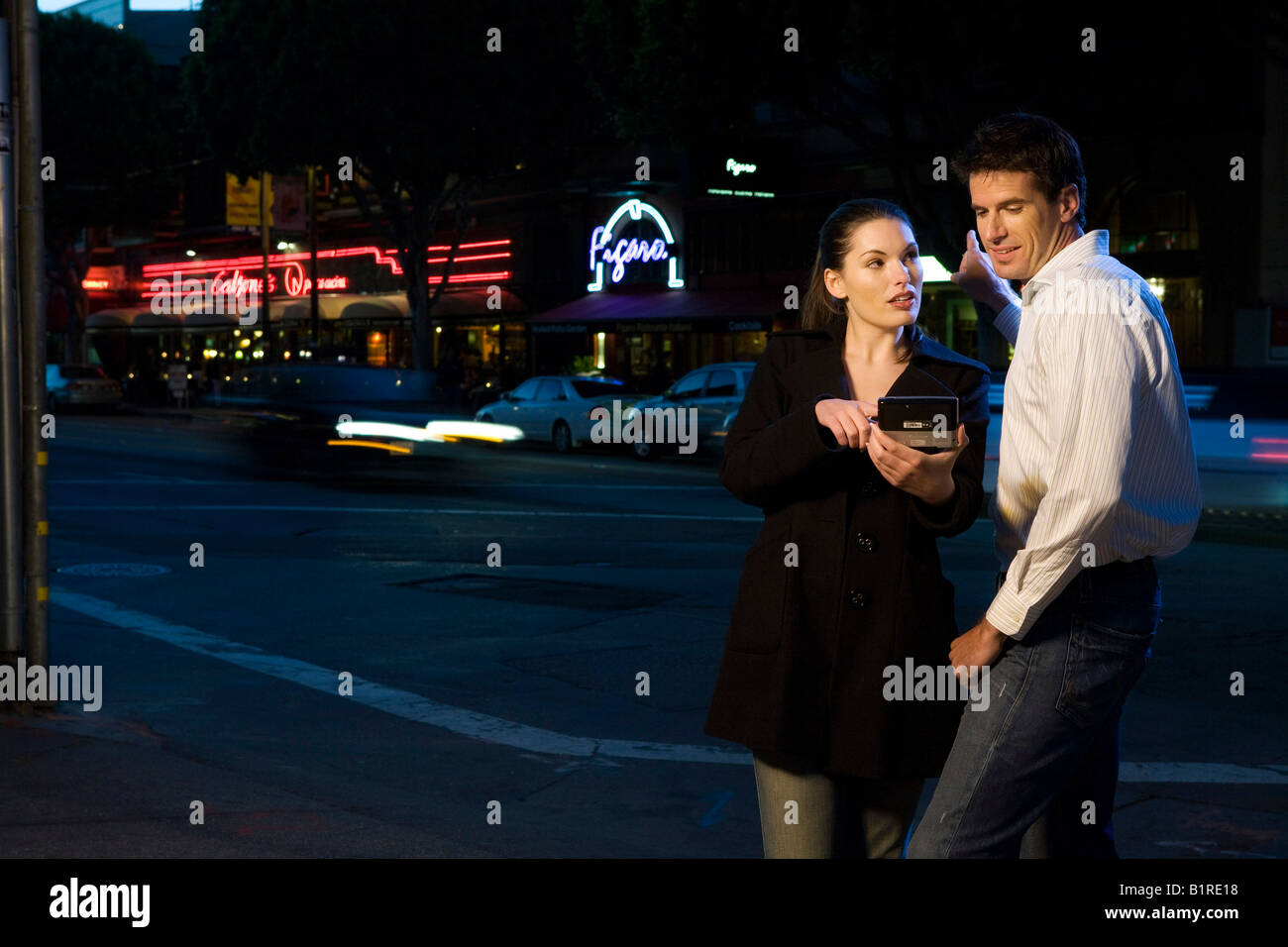A young couple are strolling through a downtown city area at night carrying a hand held device. - Stock Image