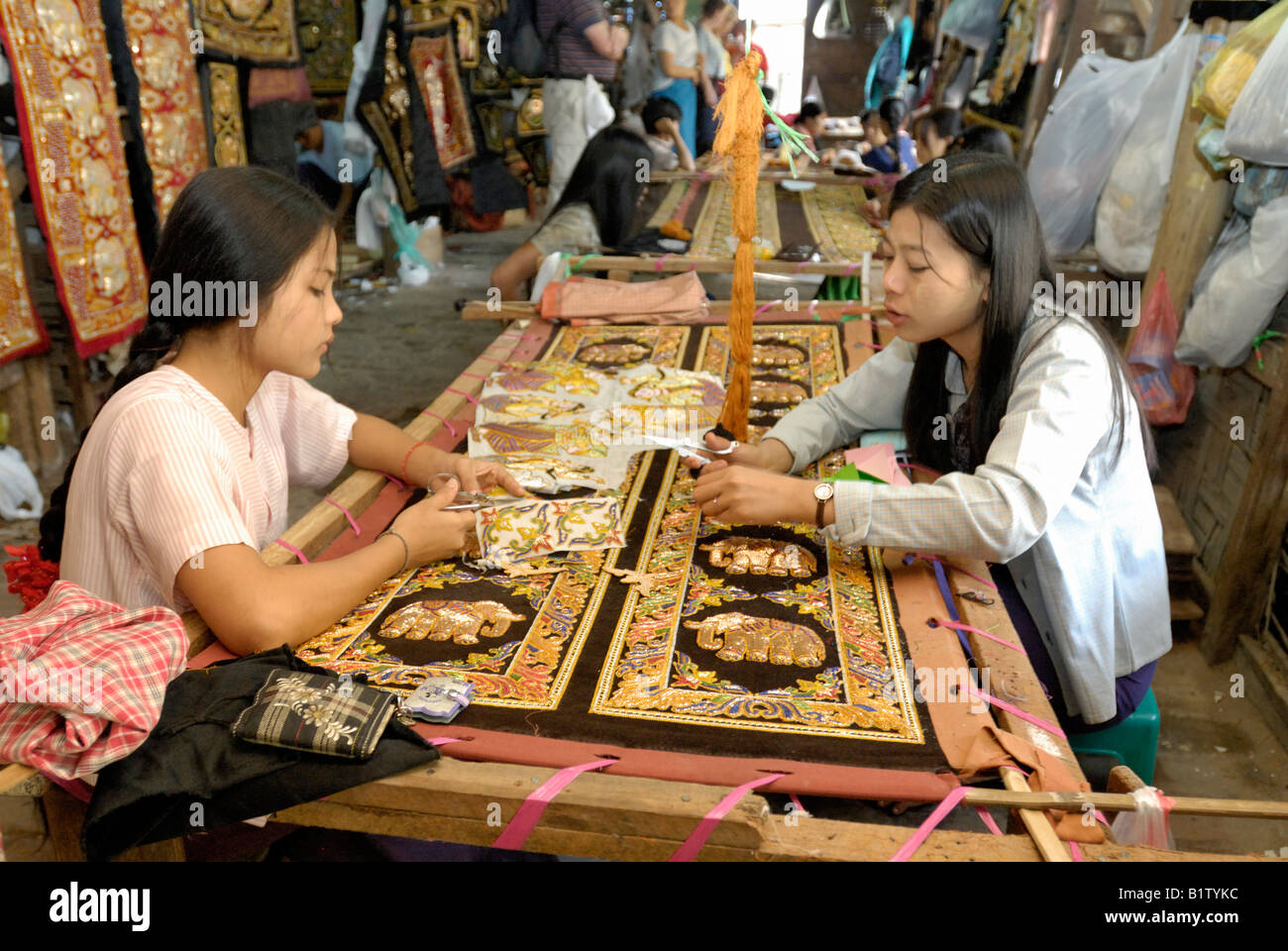 women stitching tapestries in a workshop of tapestry marionettes and other souvenirs, MANDALAY AMARAPURA, MYANMAR - Stock Image