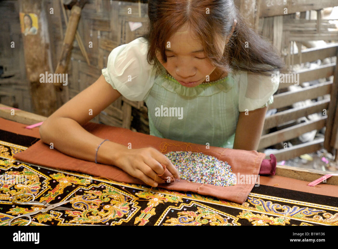 woman stitching tapestries in a workshop of tapestry marionettes and other souvenirs, MANDALAY AMARAPURA, MYANMAR - Stock Image
