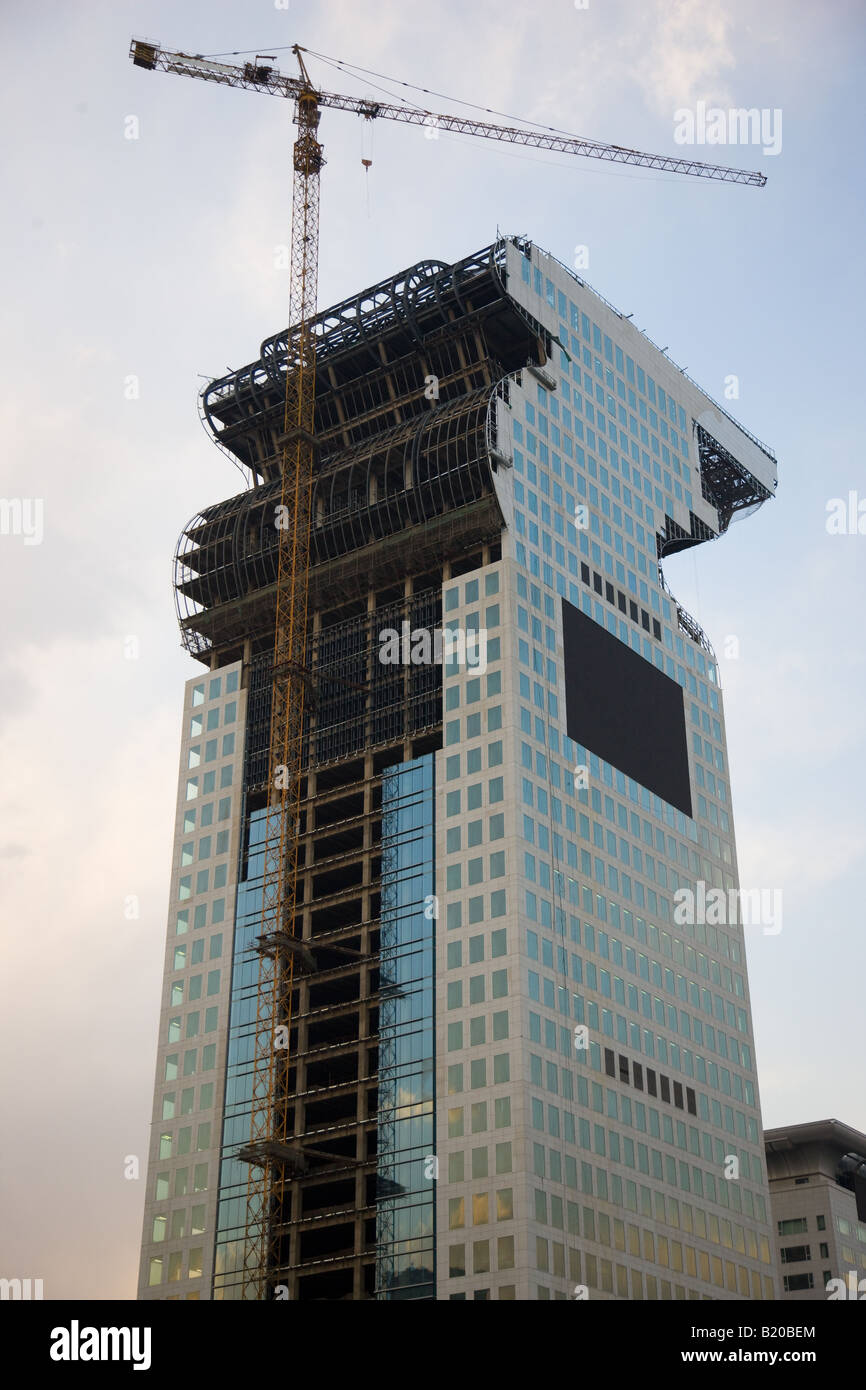 Modern glass skyscraper being built using crane at Olympic site in Beijing China - Stock Image