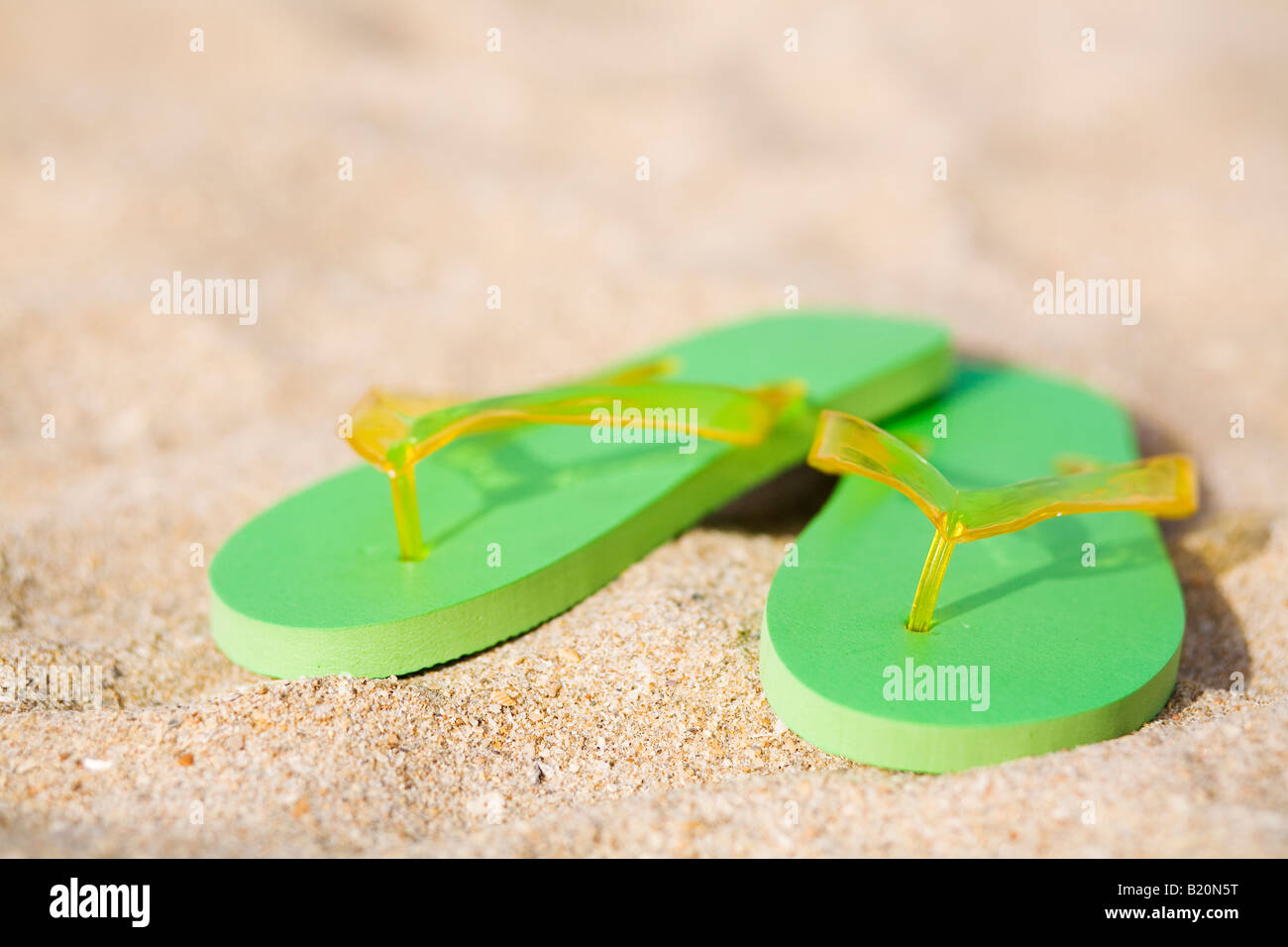 Pair of green flip flops  on the beach. - Stock Image