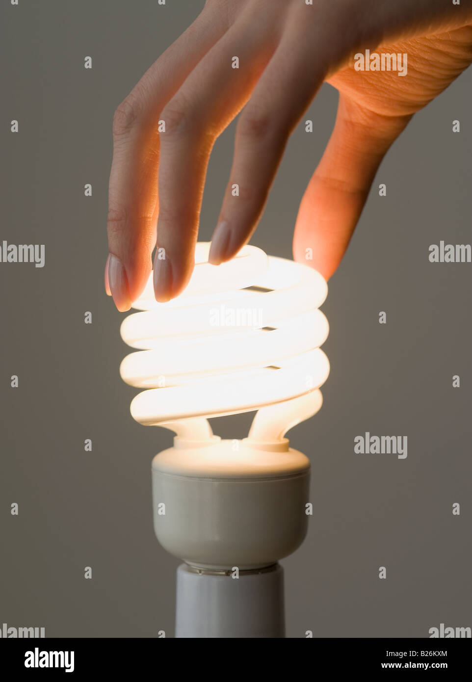 Woman screwing in energy-efficient light bulb - Stock Image
