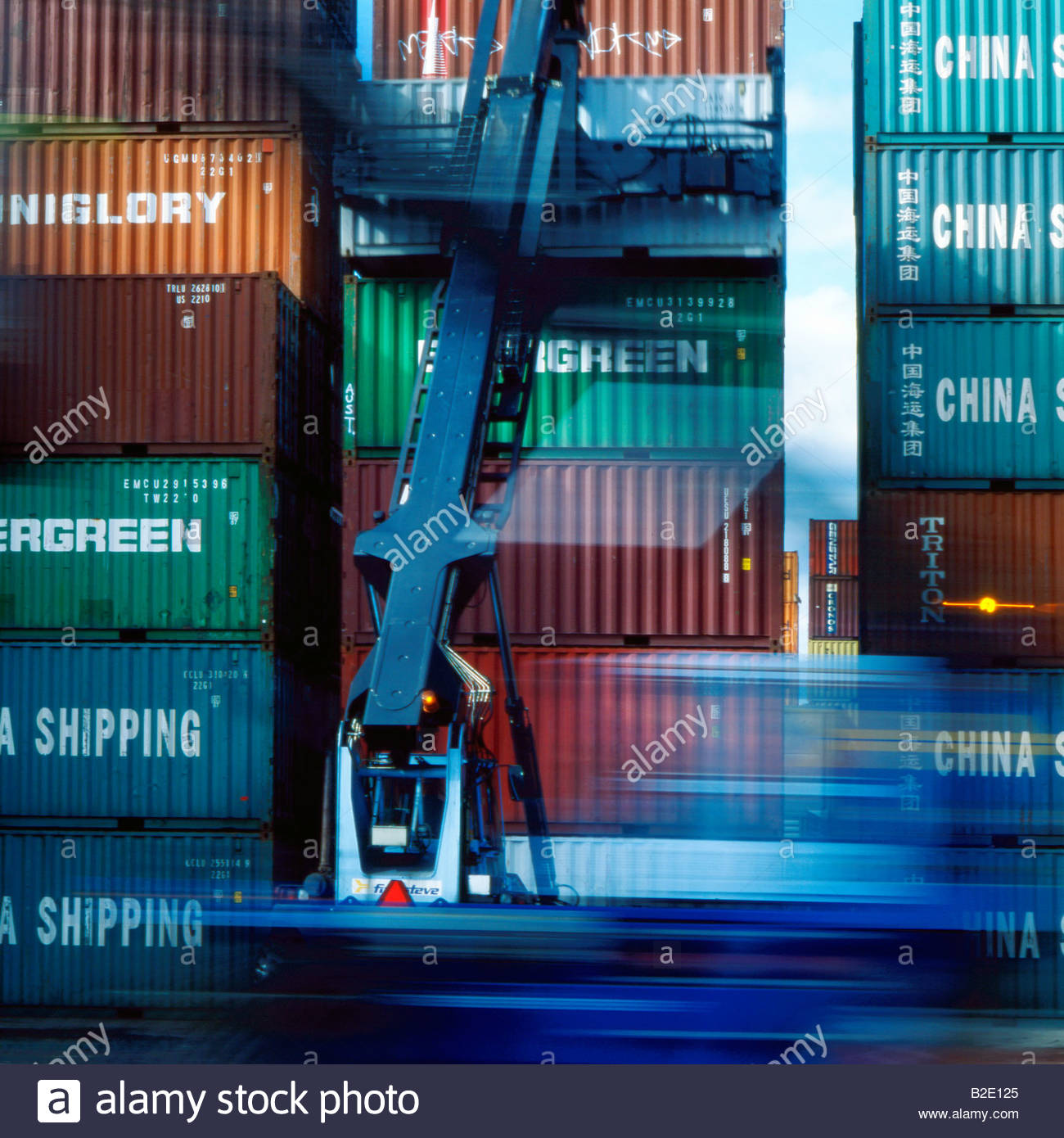 Crane in front of stacks of cargo container - Stock Image