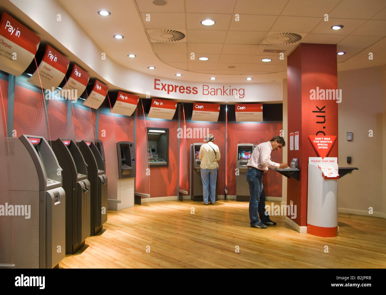 People using automated self service machines at a branch of HSBC bank Stock Photo