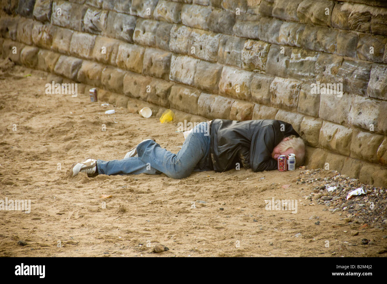 Homeless drunk man sleeping it off on the beachStock Photo