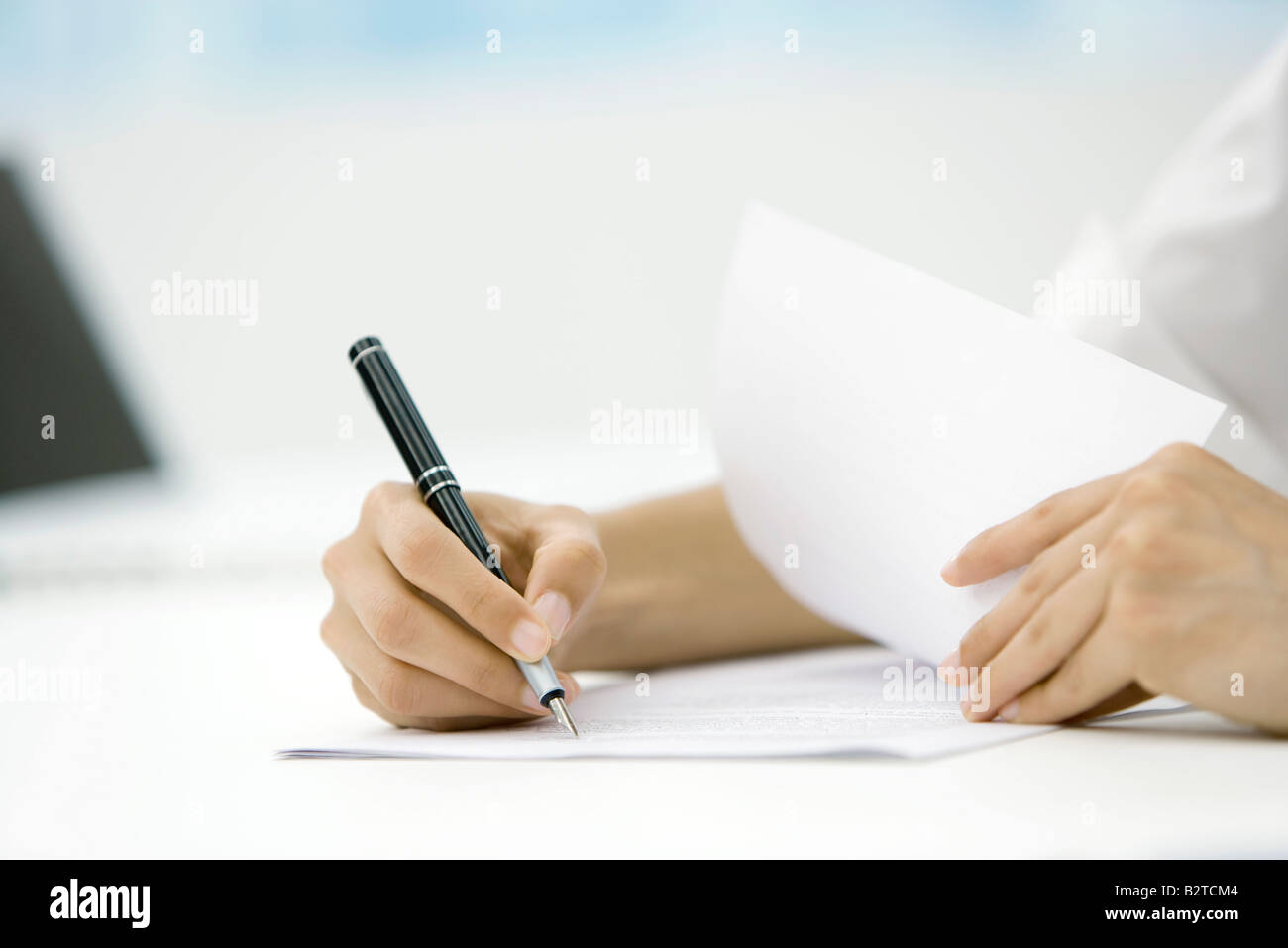 Person signing document with pen, cropped view of hands - Stock Image
