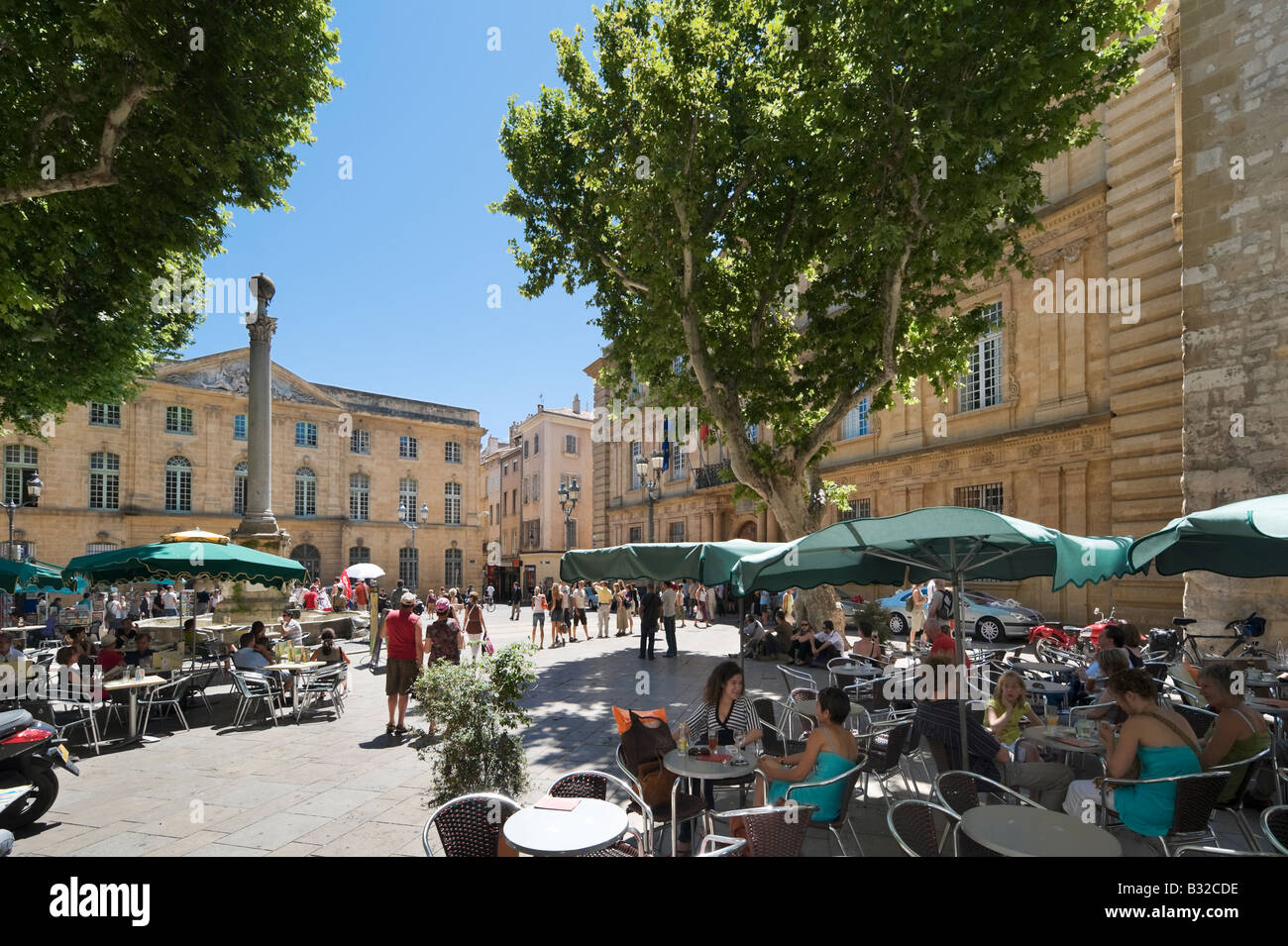 Street cafe in the Place de l'Hotel de Ville with the Town Hall behind, Aix en Provence, France - Stock Image