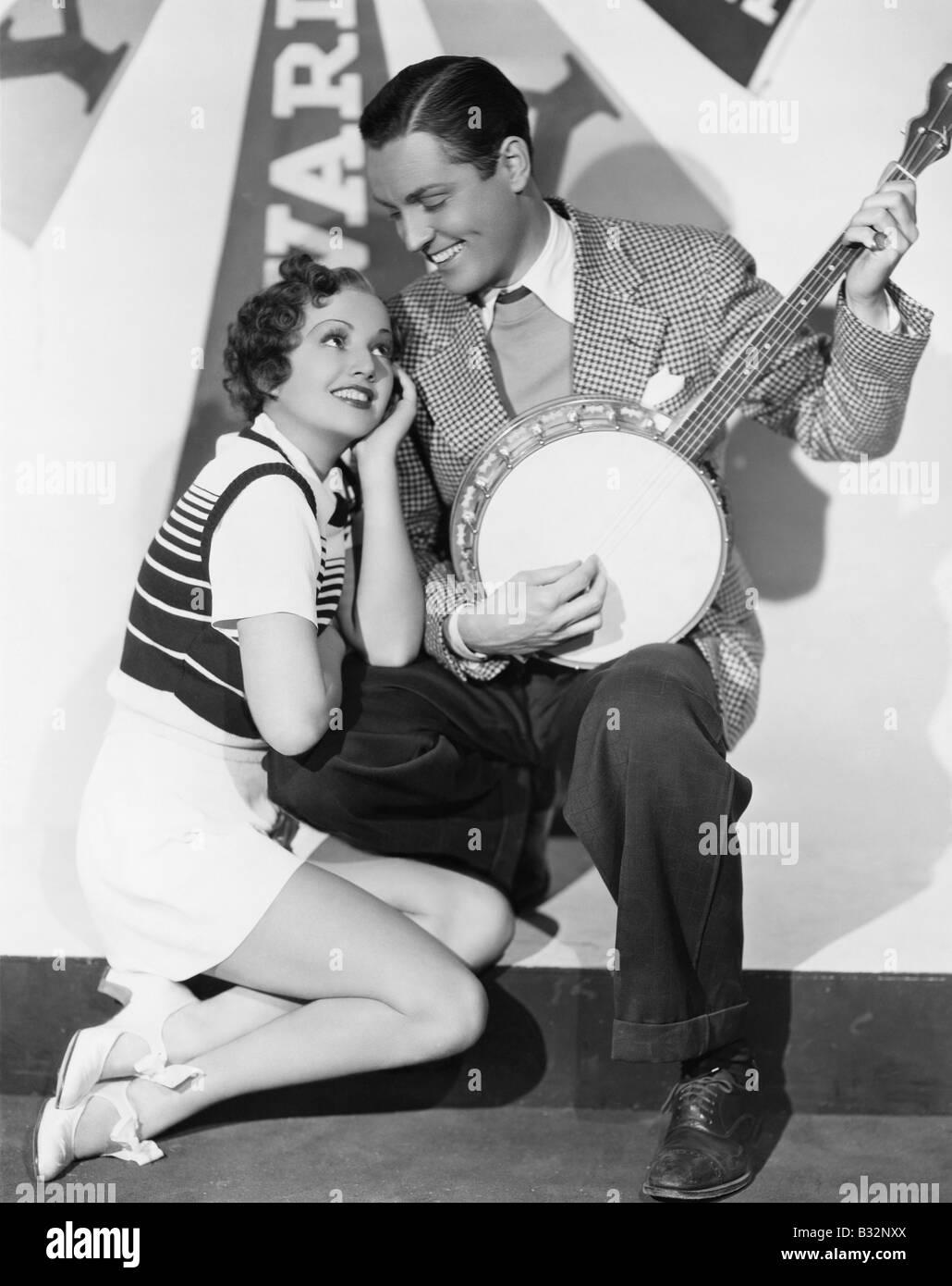 Man playing banjo for adoring woman - Stock Image
