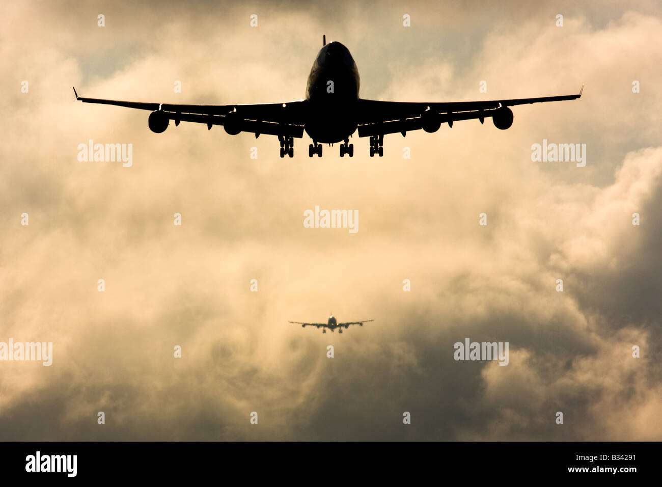 Wake turbulence forms behind aircrafts as they passes through the clouds when descending for landing. London Heathrow - Stock Image