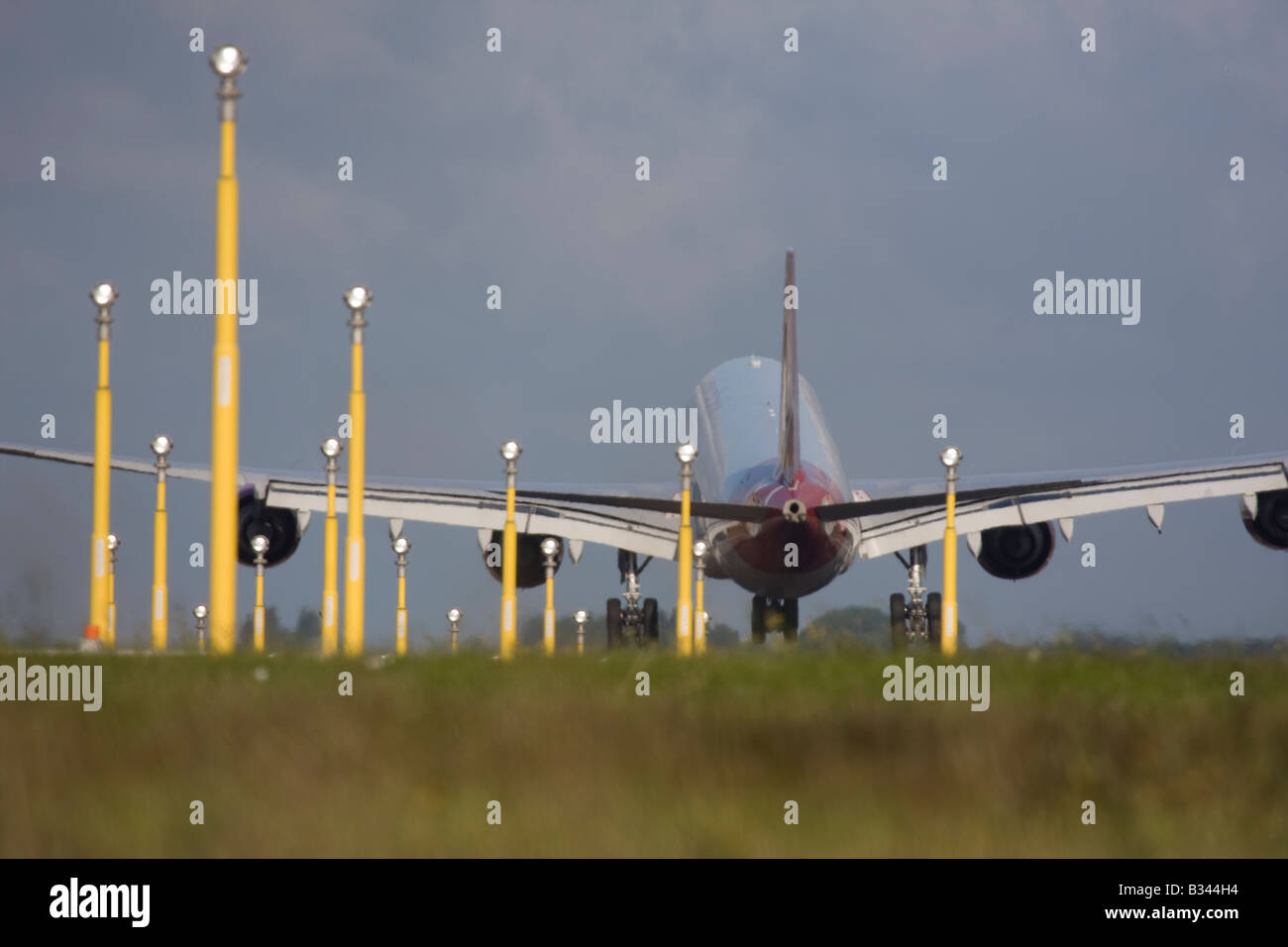 Commercial aeroplane on short final approach to London Heathrow Airport with landing lights in the foreground. - Stock Image
