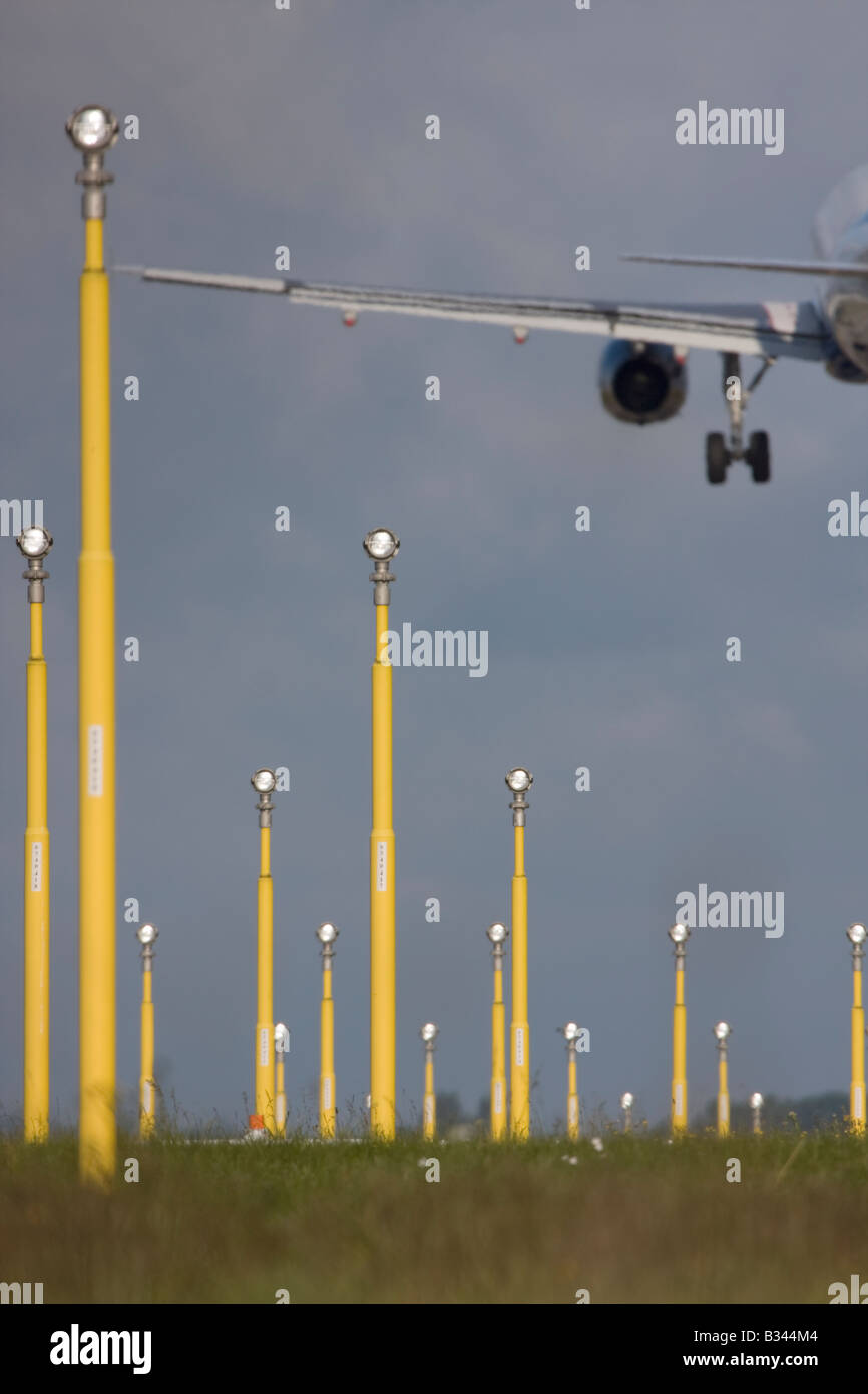Commercial aeroplane on short final approach to London Heathrow Airport with landing lights in the foreground. Stock Photo