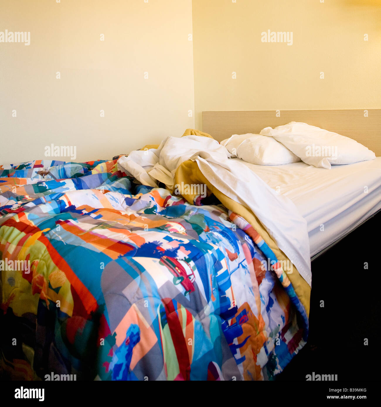 Interior shot of motel room with messy unmade bed - Stock Image