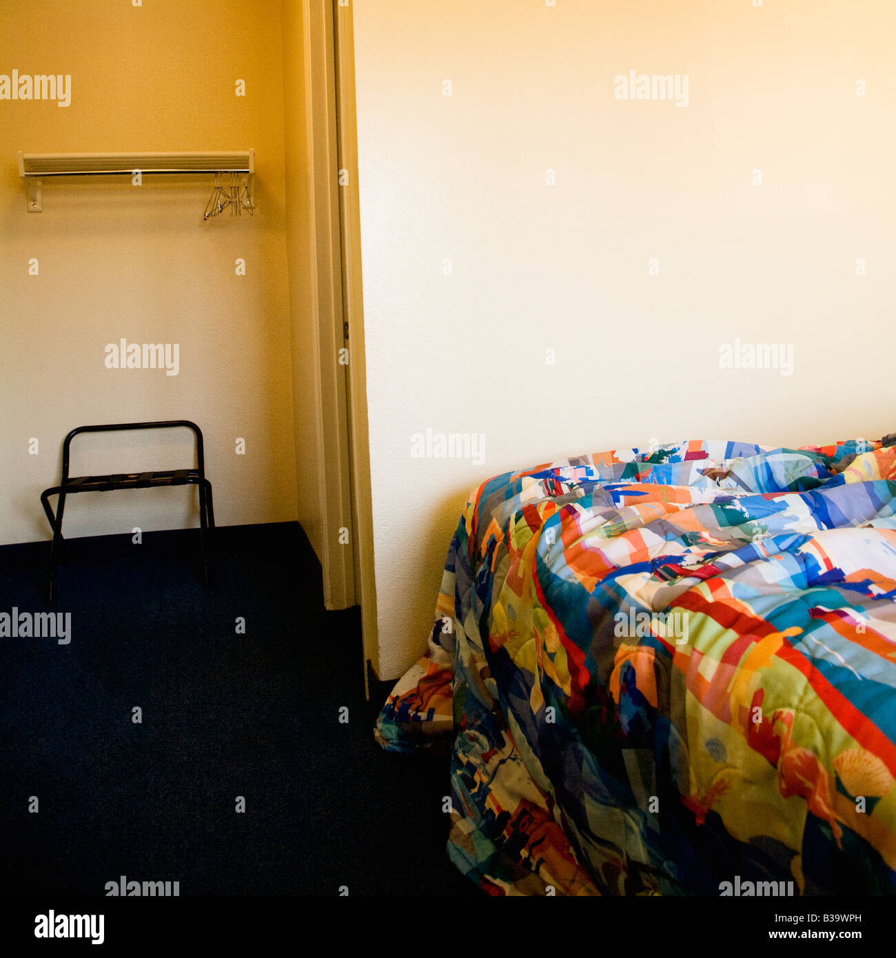 Interior shot of motel room with unmade bed and closet - Stock Image
