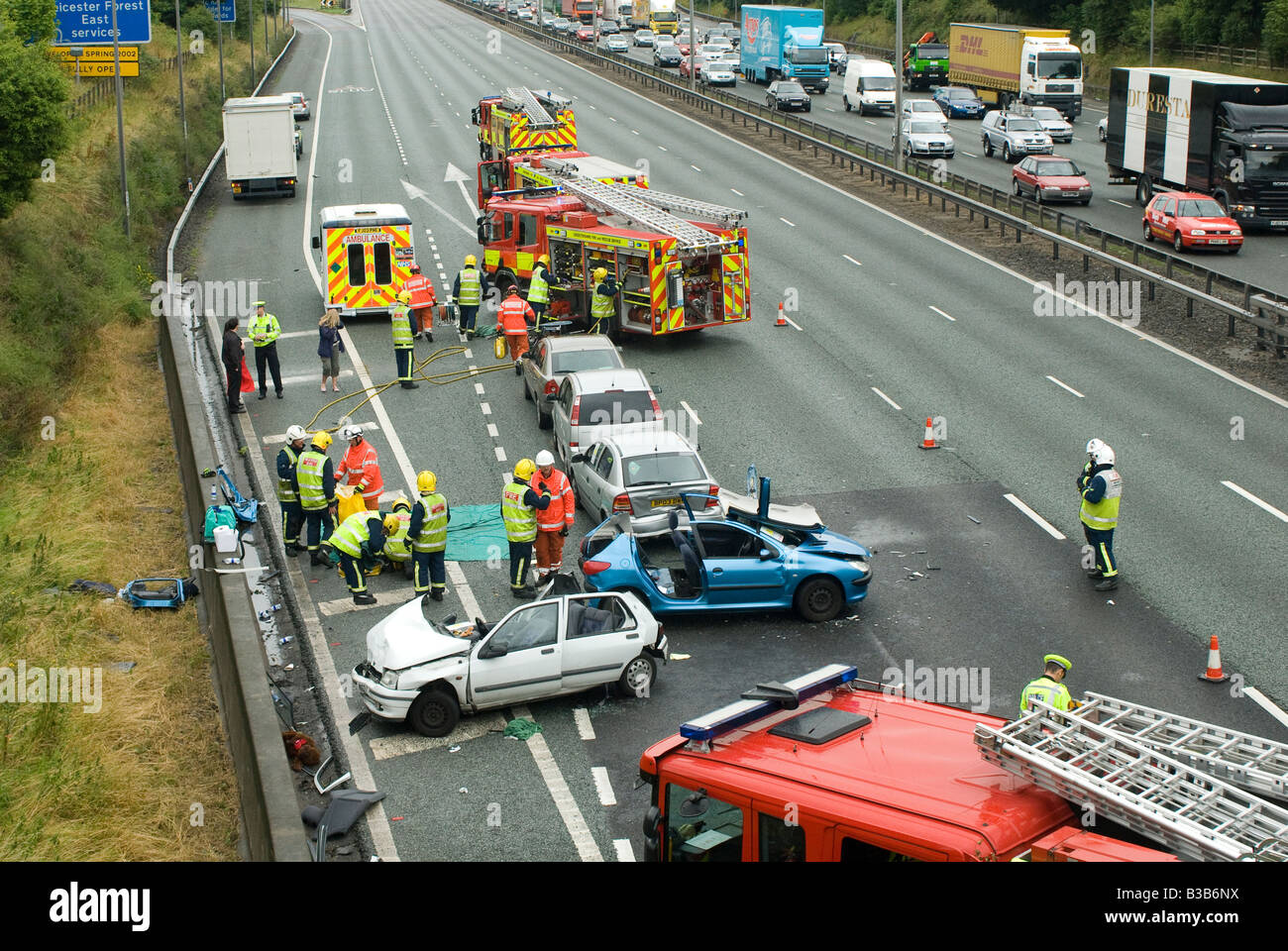 emergency services attending a nasty road traffic accident on a motorway as traffic tails back on the opposite carriageway - Stock Image
